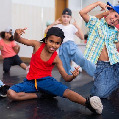 Positive girls and boys training hip hop in dance studio, dance classes for kids