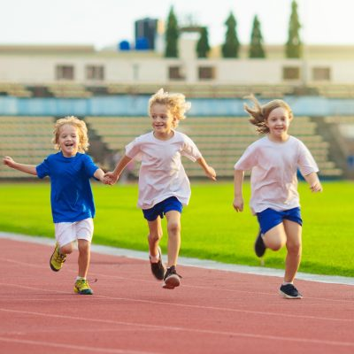 Child running in stadium. Kids run on outdoor track. Healthy sport activity for children. Little girl at athletics competition race. Young athlete in training. Runner exercising. Jogging for kid.