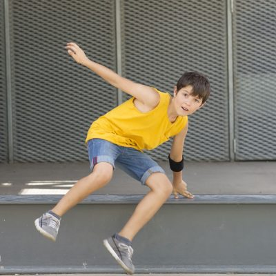 Front view of a smiling boy jumping over a metallic fence while looking camera on a bright day