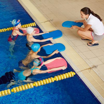 Little swimmers in water looking at their coach